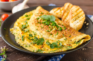Herb omelette with chives and oregano sprinkled with chili flakes, garlic panini toasts