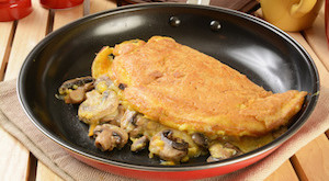 An omelet with sauteed mushrooms and cheeses in a frying pan