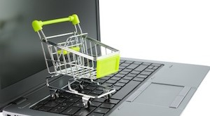 Concept of online shopping with miniature shopping cart on keyboard
