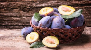 Fresh plums on wooden background .