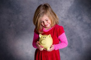 portrait of a smiling girl with piggy bank