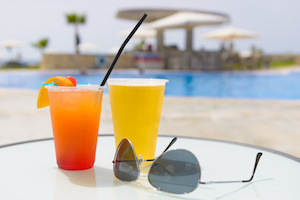 Refreshing summer cocktails and a pair of sunglasses on a table beside a swimming pool at a vacation resort.