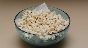 Homemade popcorn in a glass bowl on an oil obsreving tissue paper