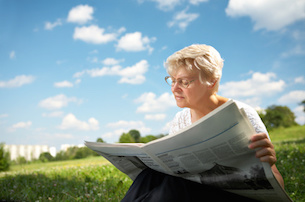 The woman in old age sits on a grass in park on a background of the blue sky and reads the newspaper