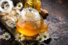 fragrant chamomile tea in a glass teapot on dark background, horizontal