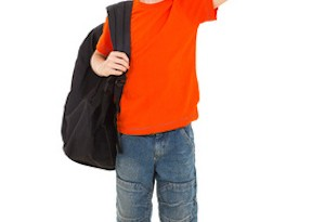 smiling schoolboy with backpack waving goodbye