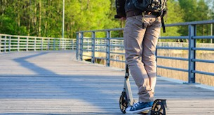 Young man in casual wear on kick scooter in park at sunset