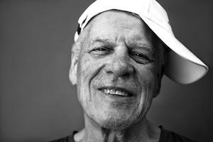Black and white portrait of a happy senior in a cap, studio shot