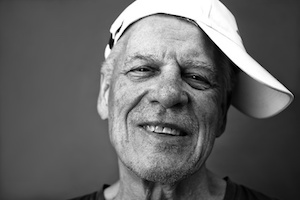 Black and white portrait of a happy senior in a cap, studio shot