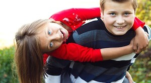 Siblings having fun - boy carrying his sister on his back.