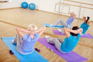 Mature females doing sit-ups on mats in sport gym