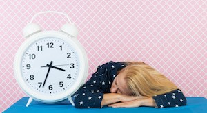 Woman of mature age laying next to big alarm clock