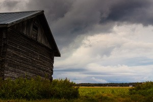 An old barn house against the stormy clouds on the fields of the rural Finland.