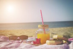 Orange juice in jar on the beach.