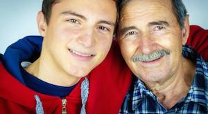 Grandfather and grandson. Teenage boy hugging grandfather