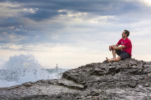 Kroatien, Istrien, Kap Kamenjak, Mann sitzt auf den Felsklippen und schaut entspannt auf die Brandung
