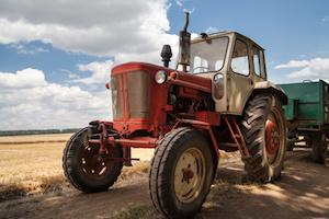old tractor on the field, against a cloudy sky