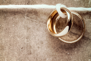 Wedding rings hanging on rope over a dirty canvas background