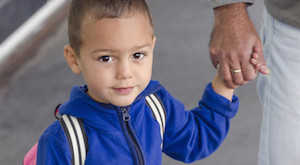 Portrait of  child toddler, boy or girl, holding a hand of father.