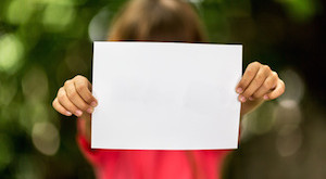 Blurred girl holding a blank piece of paper with copy space in front of her.