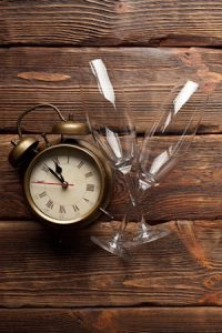 Alarm clock and two empty glasses on wooden background