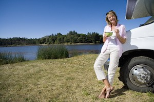 Woman with bowl by motor home and lake, smiling, portrait, low angle view