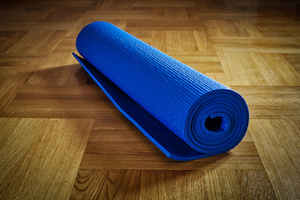 Yoga background - yoga mat on wooden floor